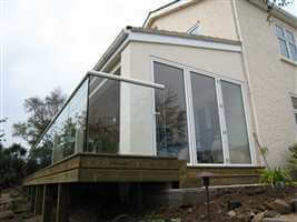 White handrail on semi frameless structural glass balustrade