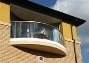 Luxury apartments in Streatham, London make a distinctive architectural statement with Balcony's Curved Clear Glass Balconies.