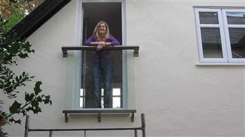 Woman leaning on her small Royal Chrome Juliet balcony