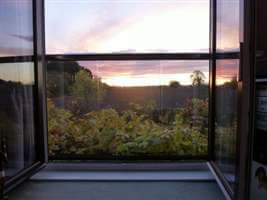Sunset view through a Juliet balcony with Royal Chrome handrail
