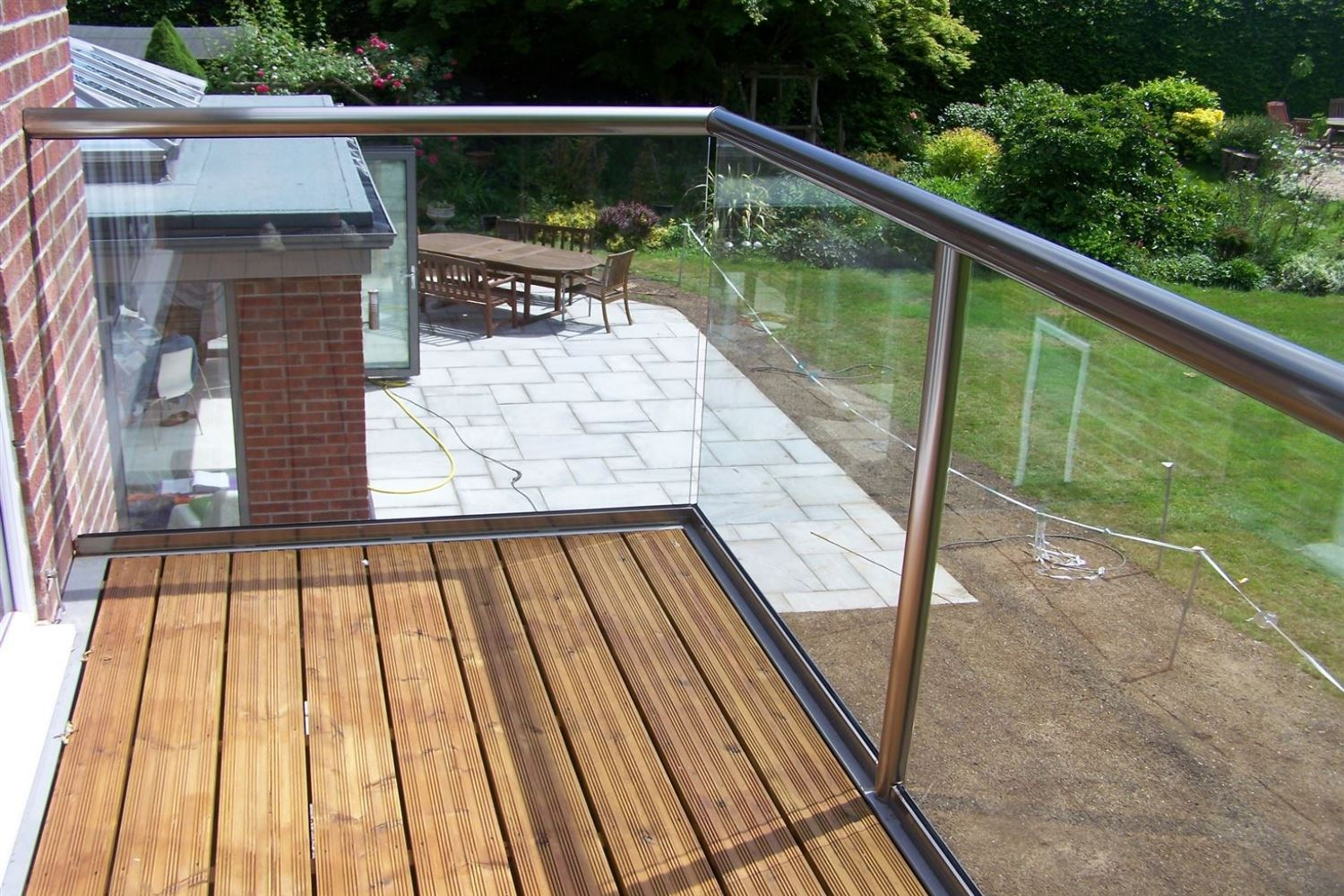 Orbit Royal Chrome Glass Balustrade overlooking a garden view with a patio