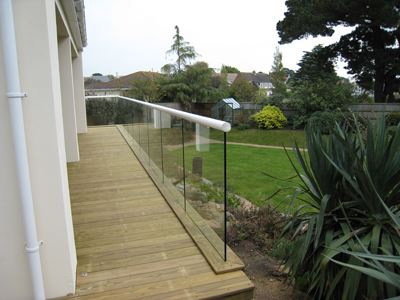 The end of a White Orbit Glass Balustrade installed in a garden