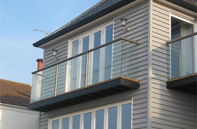 Short clear glass Bronze balcony on the side of a pretty house