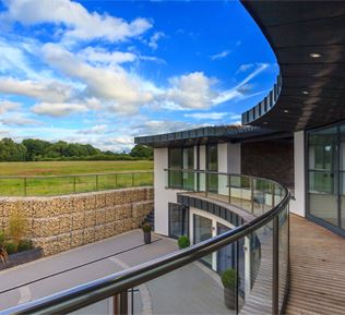 Curved Orbit Glass Balustrading overlooks the grounds at this striking two-storey property standing over eight acres on the site of a former piggery near the village of Slinfold