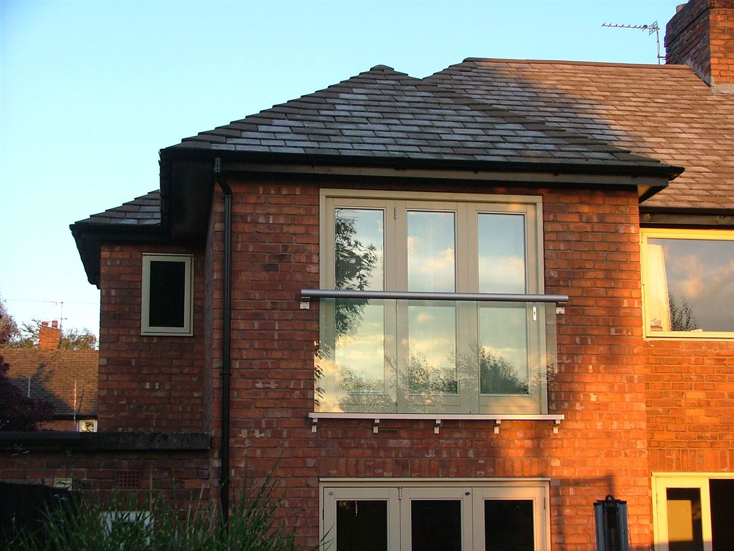 Glass Juliet Balcony installed on a brick house