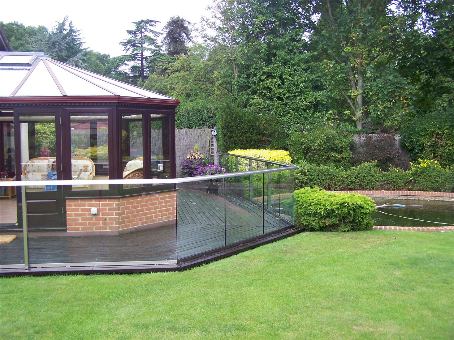 Aerofoil Glass Balustrade overlooking the well manicured garden with a pond