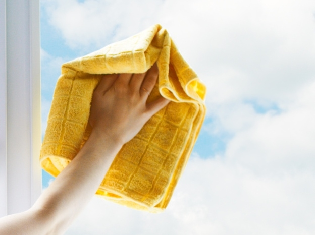 Wiping clean a dirty window with the Microfibre cloth and heavy duty cleaner