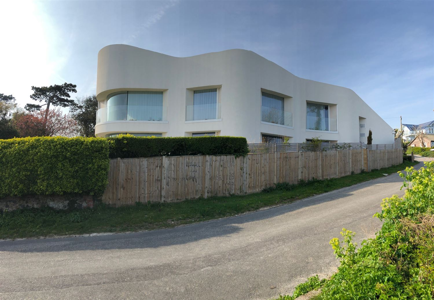 Curved Frameless Glass Balustrade installed on a modern property with cream exterior paint work.
