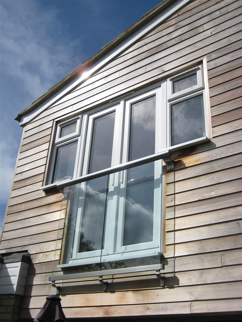 Royal Chrome Orbit Juliet Balcony installed on a house with wooden cladding