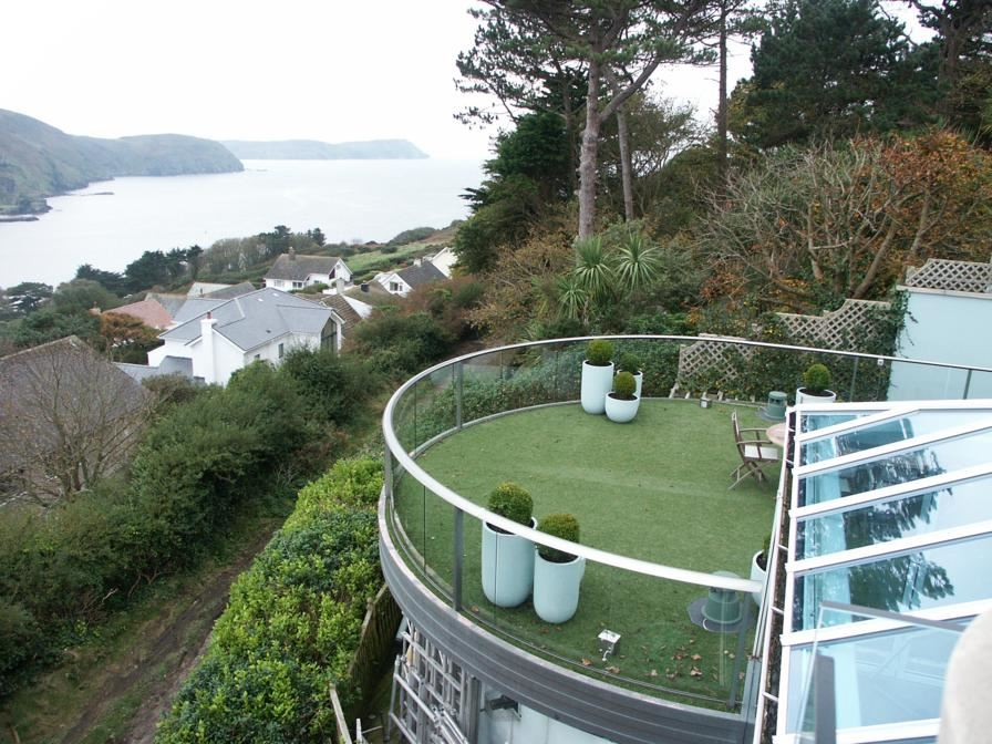 View down the hill to the water from a Curved Royal Chrome Aerofoil Glass Balustrade at this Isle of Man property